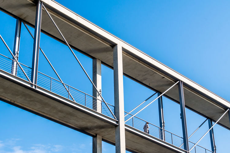 Low angle view of footbridge against blue sky