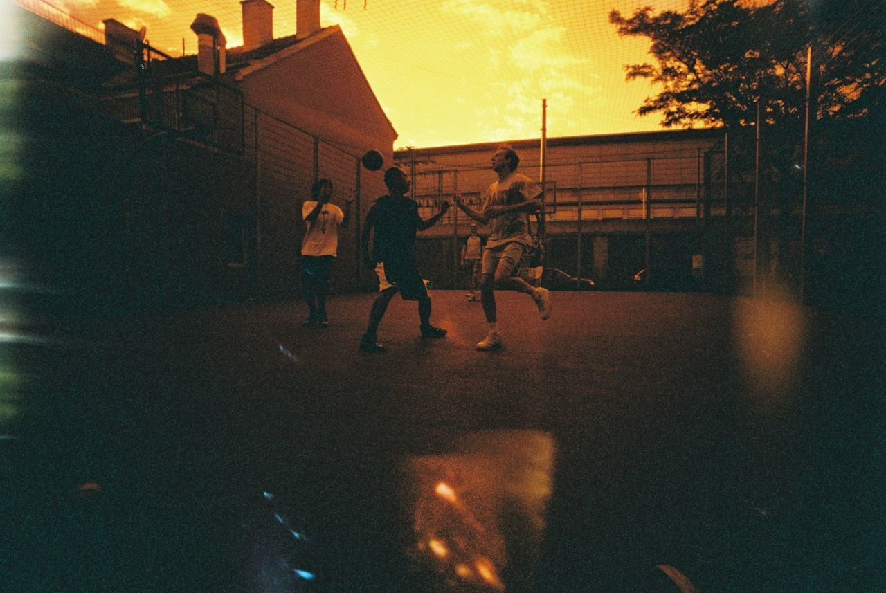 Men playing basketball on a small urban court