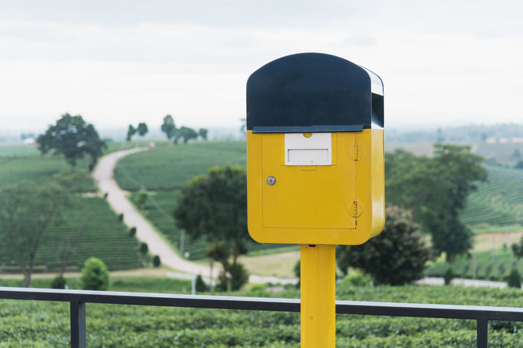 Close-up of yellow mailbox against trees and sky