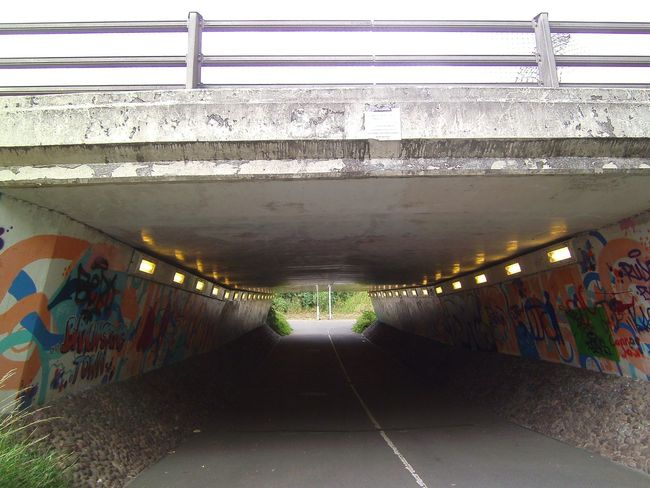 Cyclepath and footway under major road with graffit Underpass Architecture Bridge Built Structure Cyclepath Cycleway Graffiti Illuminated No People Subway Tunnel