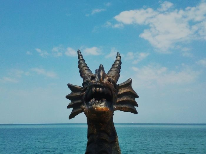 Dragon sculpture by sea against sky