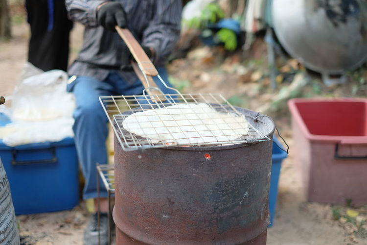 Low Section Of Man Preparing Food On Barbecue Grill