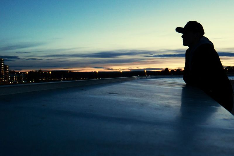 Side view of silhouette man sitting on road at sunset