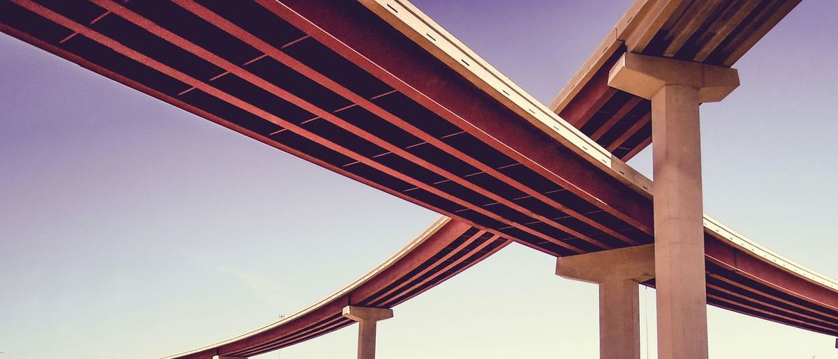 Low angle view of modern bridges against clear sky