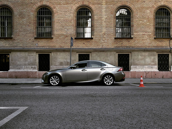 Digital composite image of car on road by building