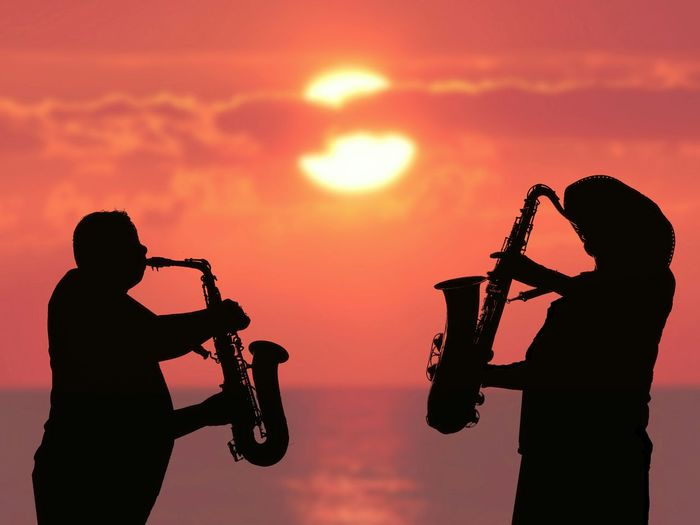 Silhouette 2 musician men with saxophones are playing jazz music with blurred sea view in sunrise sky background on entertainment and lifestyles concept Men Reflection Sea View Foreground Lifestyles Party Celebration Outdoor Blur Background Musical Relaxing Playing Sunset Sunrise Morning Evening Sundown Male Saxophone Sunset Togetherness Silhouette Friendship Sky Brass Instrument  Jazz Music Wind Instrument Saxophonist Blues Music Musical Instrument