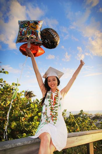 Portrait Of Smiling Young Woman Wearing Mortarboard Holding Balloons While Sitting On Railing Against Sea At Beach