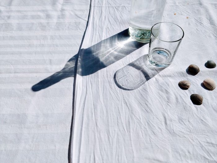 High Angle View Of Drinking Glasses And Seashells On Table