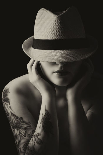 Close-up of shirtless young woman wearing hat against black background