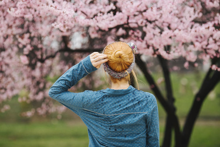 Low section of man standing by cherry blossom tree