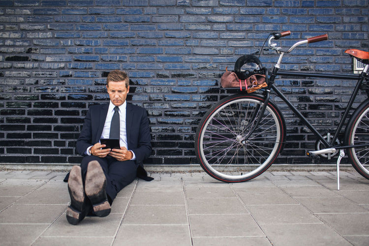 Man sitting on bicycle against brick wall