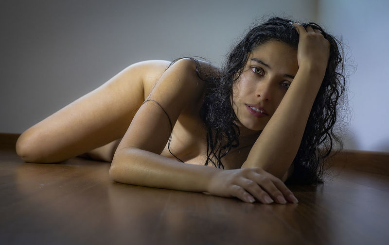 Portrait Of Sensuous Naked Woman Lying On Floor At Home