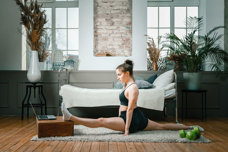 A strong and beautiful sports fitness girl in sportswear stretching and doing twine in her bright