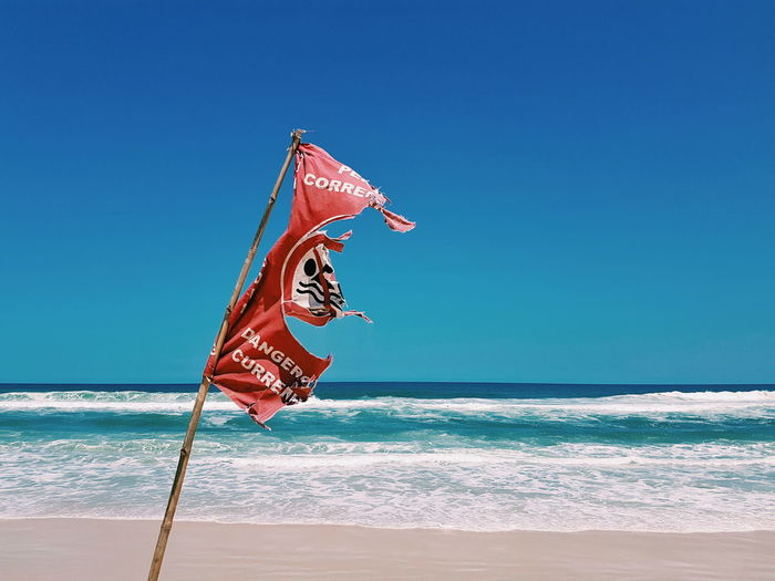 Torn Flag At Beach Against Clear Blue Sky