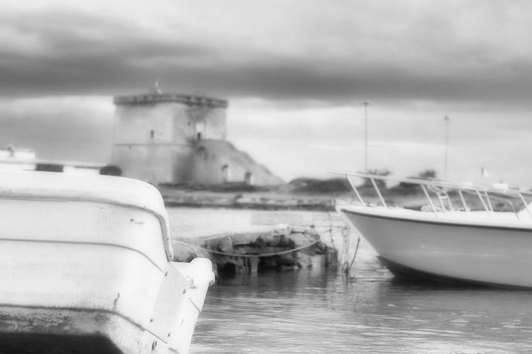 Boats moored in sea against buildings