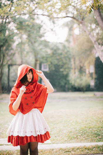Young woman wearing red hood while standing in public park