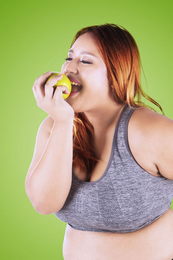 Smiling Young Woman Eating Fruit Against Green Background