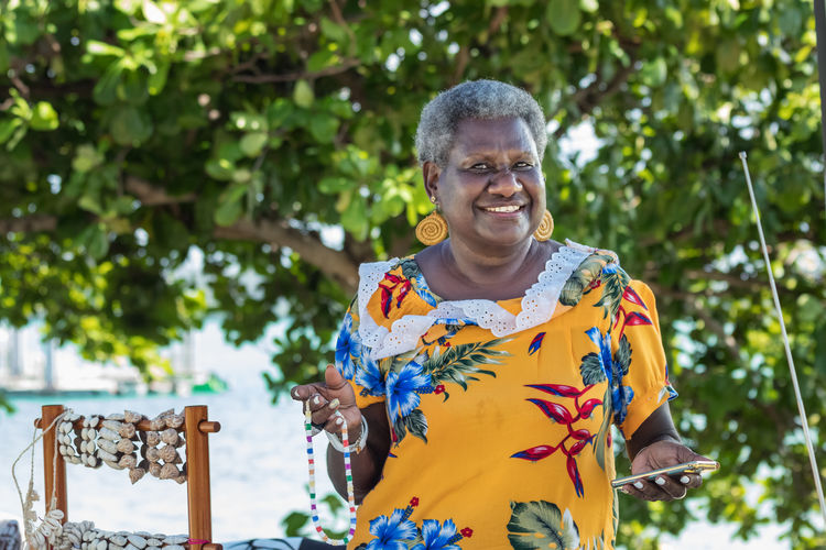 Portrait of smiling melanesian woman standing against plants