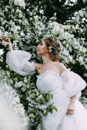 A beautiful delicate elegant young woman bride in a wedding dress walks in a blooming spring park