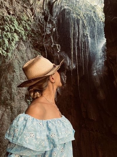 Woman wearing hat standing in cave