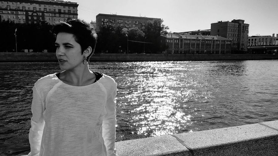 Thoughtful young woman standing against river in city