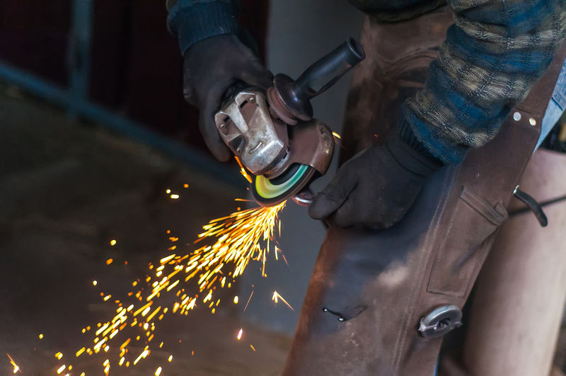 Blurred Motion Effort Hand Heat - Temperature Holding Human Body Part Human Hand Industry Iron - Metal Metal Metal Industry Motion Occupation One Person Protection Protective Workwear Real People Skill  Sparks Welding Work Tool Working