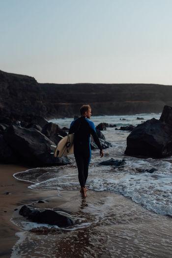 Full length of man on rock at beach against clear sky