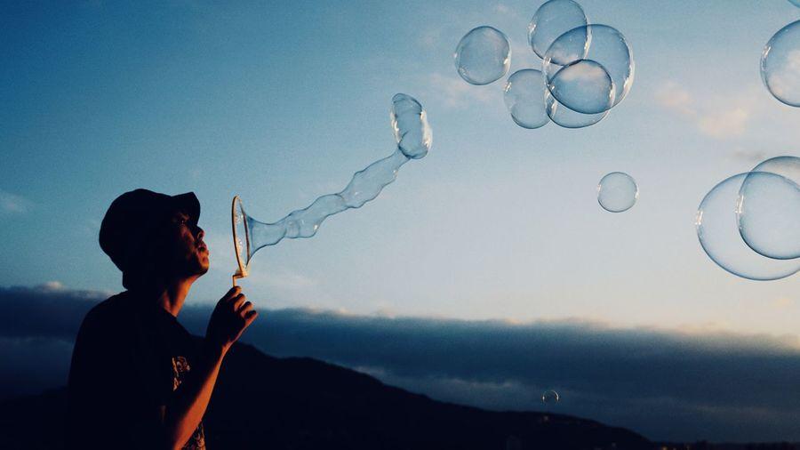 Man blowing bubbles against blue sky