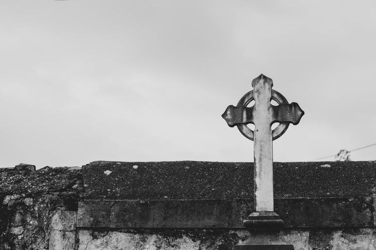 Low angle view of cross on wall against sky