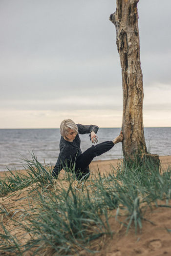 Woman sitting on shore by sea against sky