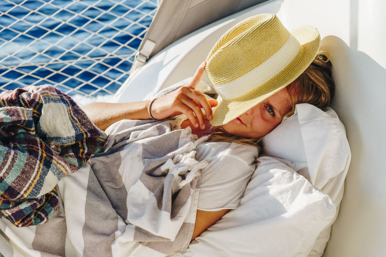 Woman Smiling Happy Happiness Calm Hiding Looking At Camera Hat Lying Down Yacht Sailboat Sailor Traveler Young Adult Portrait Sunny Flirting Holiday Vacations Resting Sleepy Caucasian Relaxation Bed Moments Of Happiness