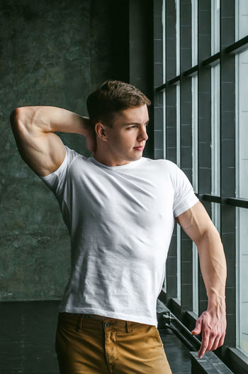 Muscular man standing by window at home