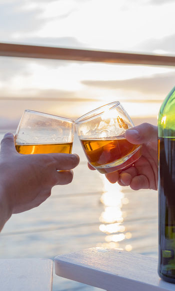 Cropped image of hands toasting against sea