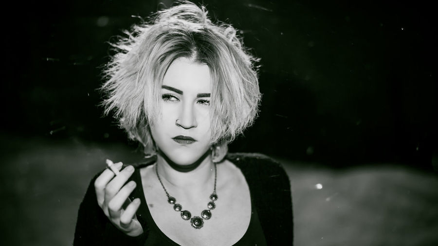 Close-up of young woman smoking cigarette at night