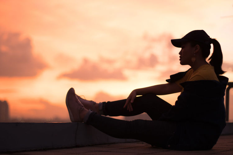 Side view of silhouette woman sitting against sky during sunset