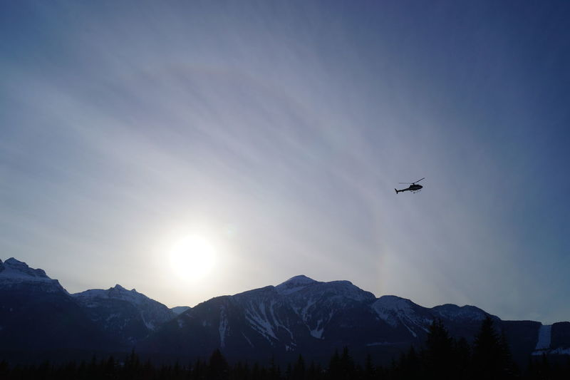 Mountain Scenics Tranquil Scene Beauty In Nature Tranquility Sun Mountain Range Transportation Nature Non-urban Scene Flying Mountain Peak Sunbeam Sky Tourism Physical Geography Majestic Vacations Outdoors High Up Sun Dog Helicopter Adventure Rocky Mountains