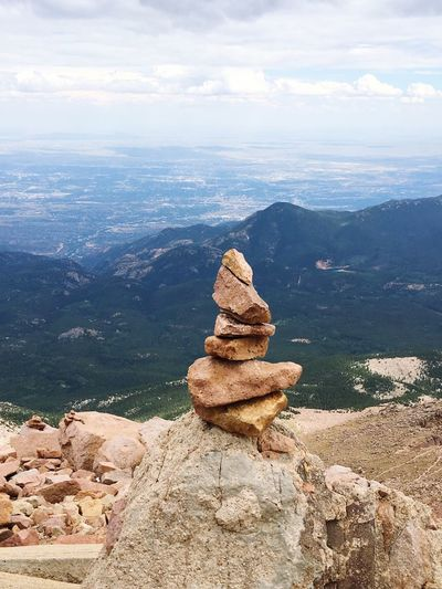 Stone stack on top of mountain against cloudy sky