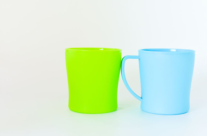 Close-up of green cup with spoon on white background