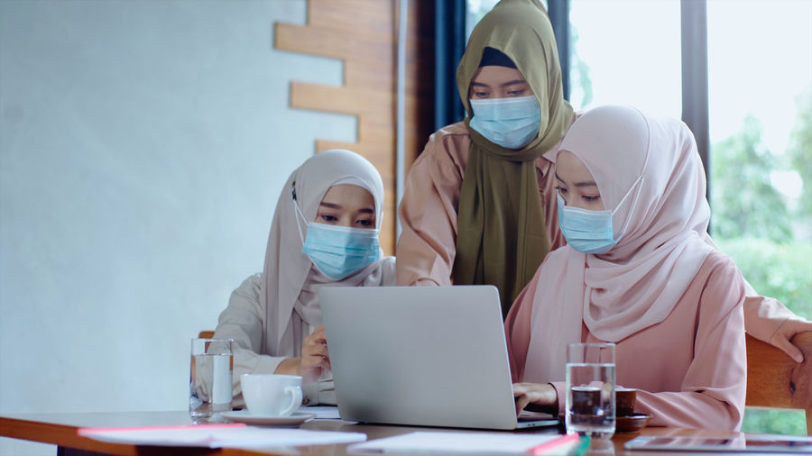 Businesswomen in hijab wearing mask looking at laptop in office