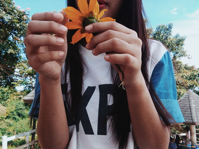 Midsection of girl holding yellow flower