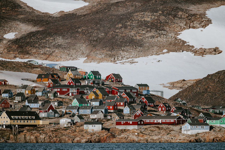 Sea by houses on snow covered mountain