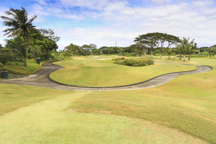 Footpath on golf course against sky