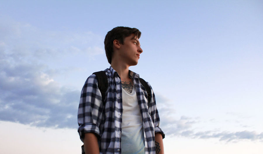 Low angle view of young man looking away while standing against sky