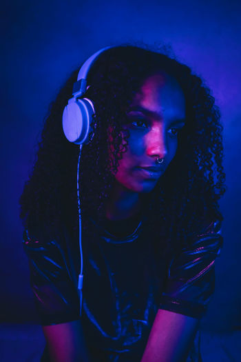 Beautiful woman with curly hair listening music through headphones in darkroom