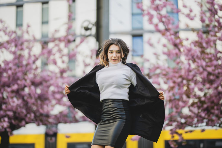 Portrait of beautiful woman holding winter coat against cherry trees in city