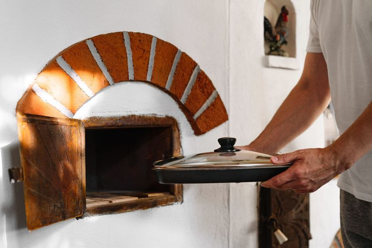 Midsection of man cooking in traditional oven