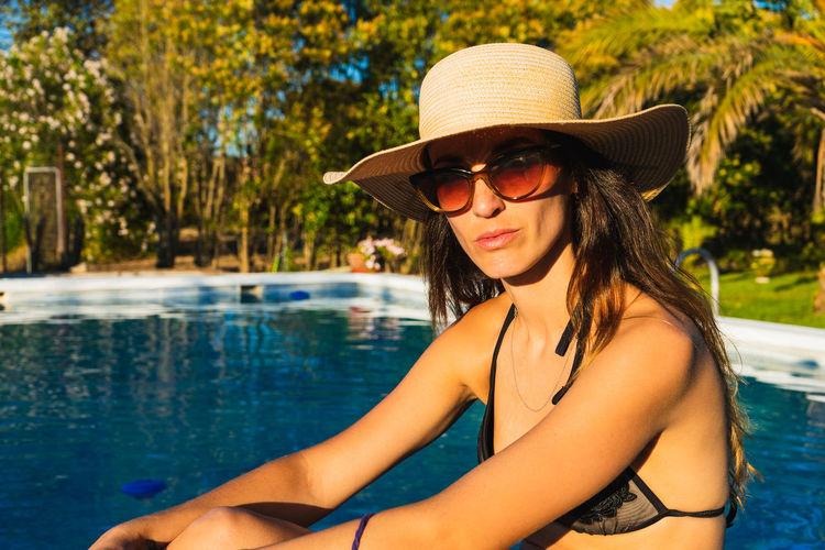 Portrait of woman wearing sunglasses in swimming pool