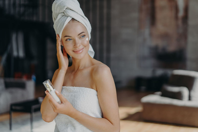 Smiling woman with perfume looking away while sitting at home