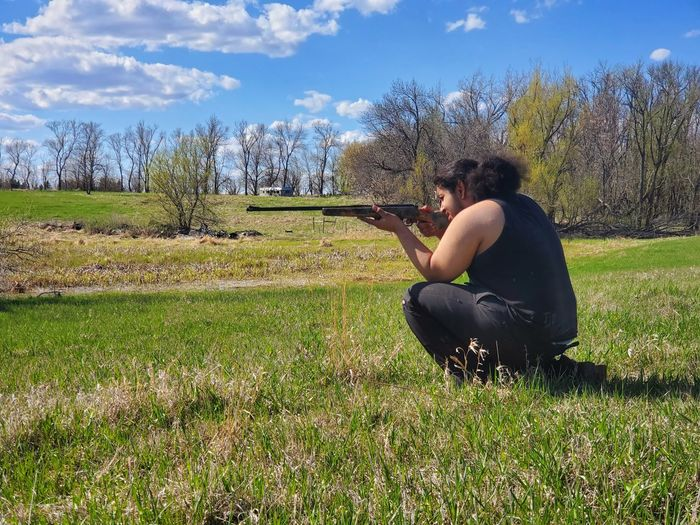 Side view of man kneeling in the country field with a rifle