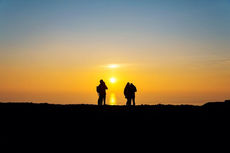 Waiting To Set Sunset Silhouette Nature Beauty In Nature Scenics Landscape Sunset #sun #clouds #skylovers #sky #nature #beautifulinnature #naturalbeauty #photography #landscape Calmness Silence Golden Hour Tranquil Scene Idyllic Tranquility Setting Sun Cliffside Cliff Edge Couple - Relationship